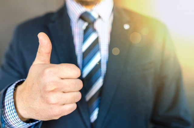 a man in coat and tie giving a thumbs up gesture