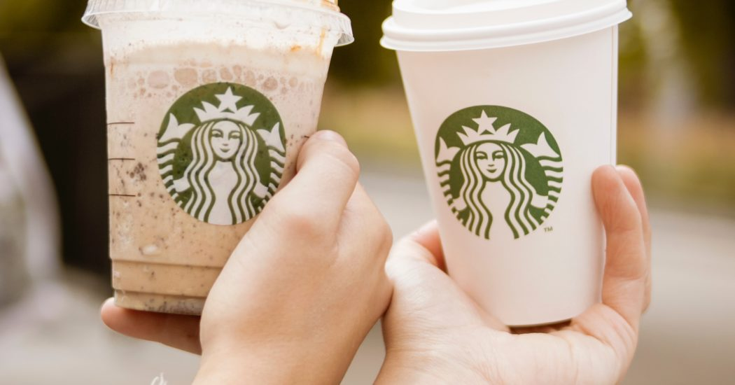 hands holding starbucks cups